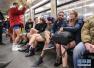 """""""不穿裤子搭地铁""""活动的参与者在地铁站候车"""