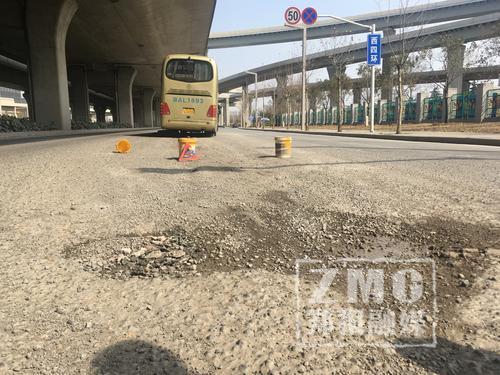 郑州西四环一马路现大坑 大巴车通过被卡路中间