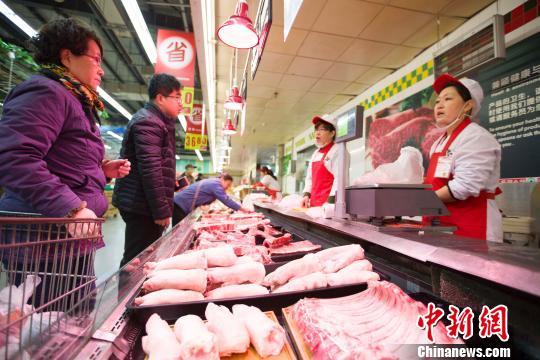 山西太原,民众正在挑选猪肉。 张云 摄