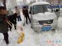 路过面包车困雪中 正扫雪的万众社区工作人员帮推车 司机感谢路人点赞