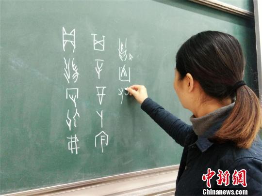 杨婷婷在黑板上书写甲骨文授课 王文 摄