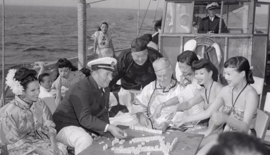 1946年,一群人在中国平地帆船上打麻将。
