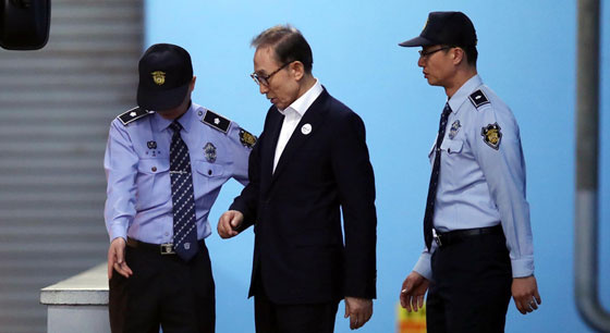 李明博首次庭审结束 在狱警搀扶下离开法院